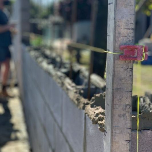 Image is of a bricklayer in Cairns profile in the foreground as a bricklayer is laying a brick fence