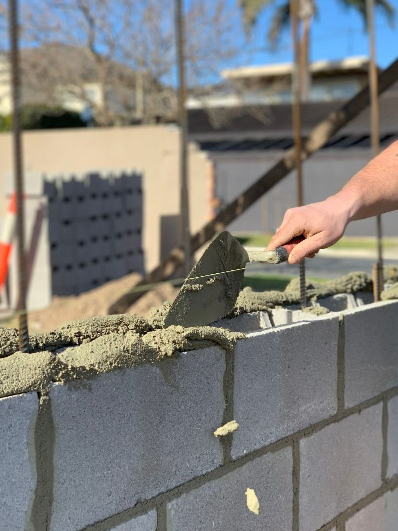 Bricklayer laying a block fence in Cairns